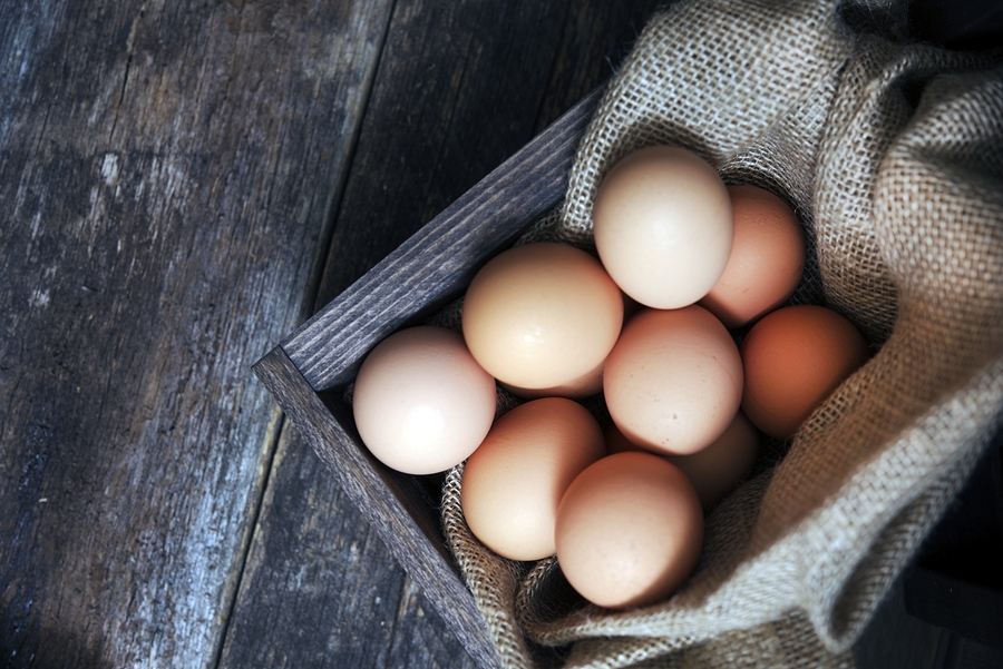 Fresh Eggs in Small Wooden Crate with Canvas on Aged Wooden Table. Fresh Organic Cage Free Chicken Eggs.
